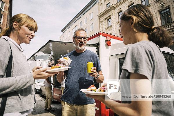 Leute  die Snacks essen  während sie in der Stadt gegen den Lastwagen stehen