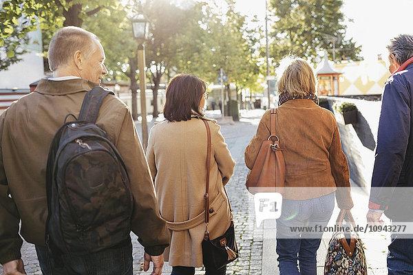 Rückansicht von Seniorenpaaren  die mit Gepäck auf dem Bürgersteig spazieren gehen.