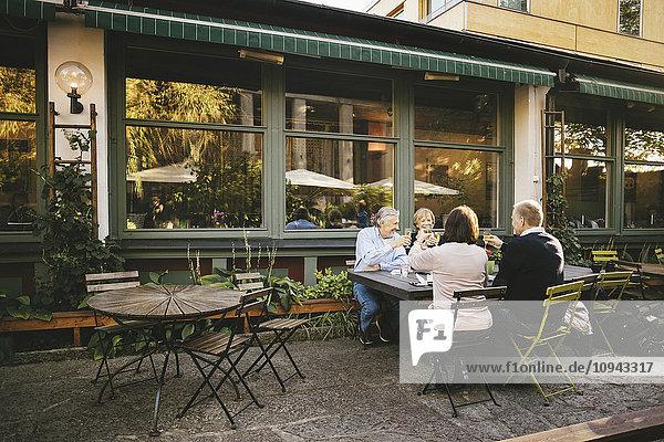 Fröhliche Seniorenpaare toasten Champagnerflöte im Außenrestaurant