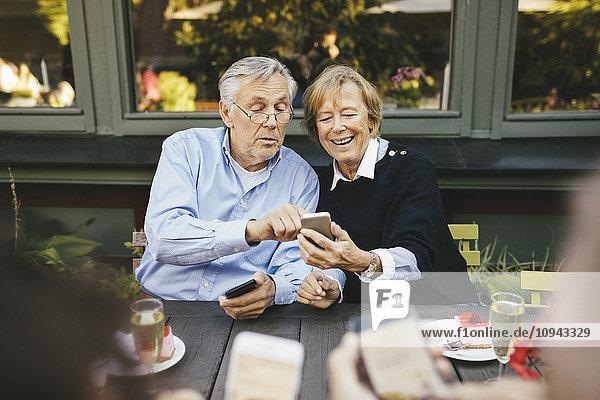 Glückliches Seniorenpaar mit Handy im Außenrestaurant