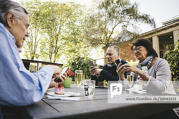 Senior people using mobile phones at table of outdoor restaurant