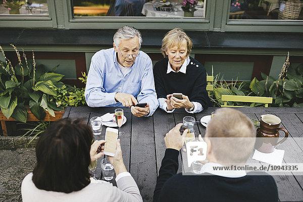 Zwei ältere Paare  die Mobiltelefone am Tisch des Außenrestaurants benutzen.