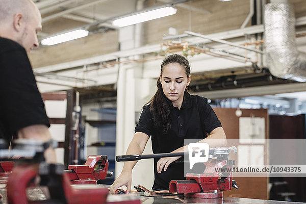 Automechaniklehrerin assistiert Schülerin in der Werkstatt