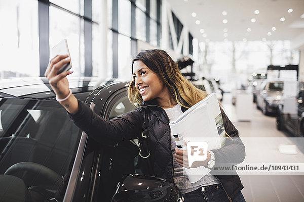 Lächelnde Frau nimmt Selfie mit neuem Auto in den Showroom