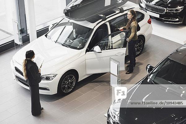 Verkäuferin beim Betrachten des Autos im Ausstellungsraum