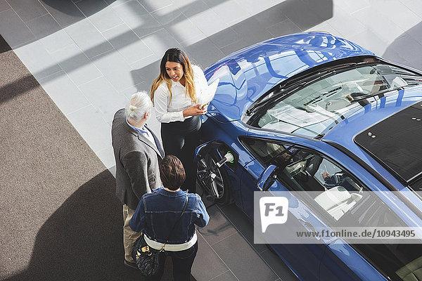 Hochwinkelansicht der Verkäuferin  die dem Kunden das Auto im Showroom zeigt.