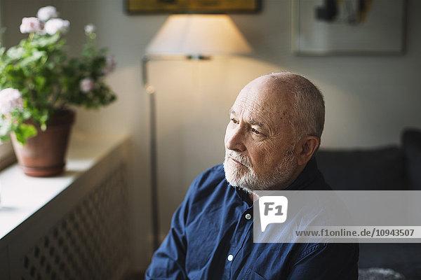 Nachdenklicher älterer Mann  der nach Hause schaut.