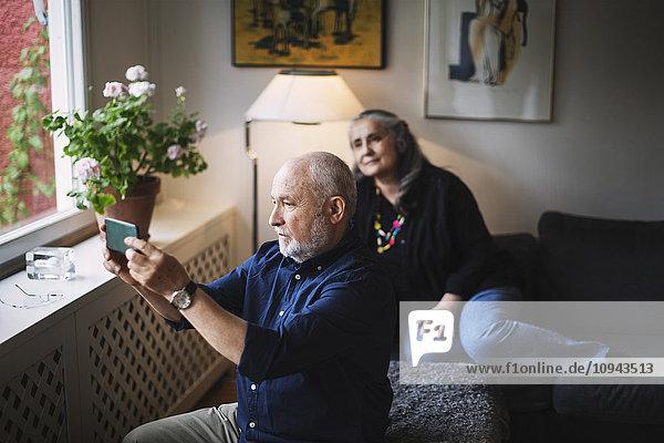 Senior Mann nimmt Selfie mit Frau über Handy mit nach Hause