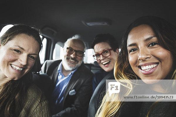 Porträt von glücklichen Menschen im neuen Auto im Showroom