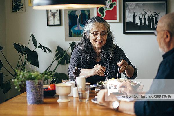 Fröhliche Seniorin beim Salat mit Mann am Tisch