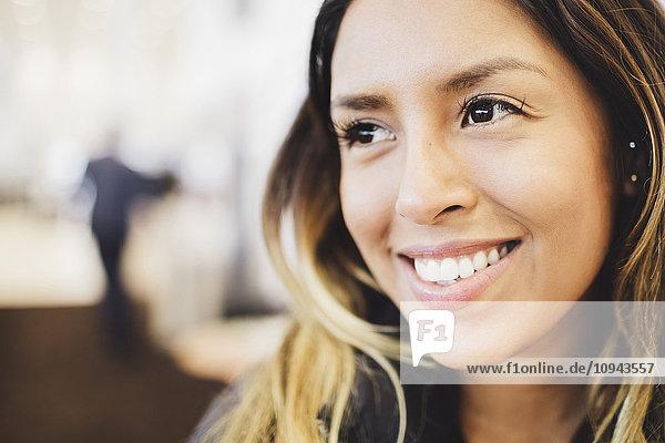 Nahaufnahme einer lächelnden jungen Frau  die wegschaut