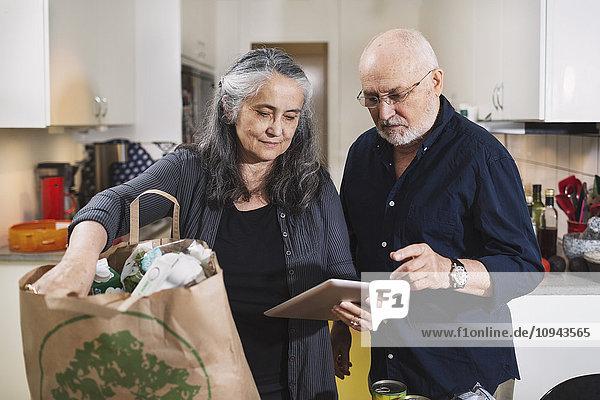 Seniorenpaar mit Einkaufstasche mit digitalem Tablett in der Küche