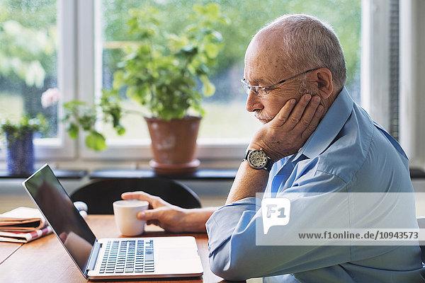 Senior Mann mit Laptop zu Hause