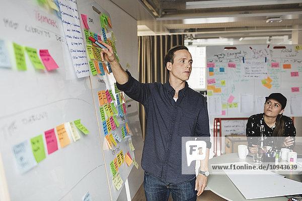 Geschäftsmann zeigt Whiteboard und erklärt Kollegen während der Besprechung im Büro