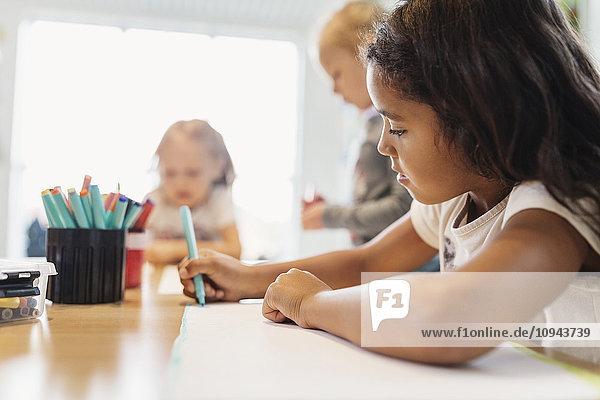 Mädchen mit Filzstift in der Zeichenklasse mit Klassenkameraden im Hintergrund