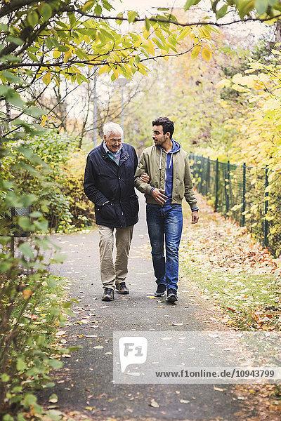 Volle Länge eines glücklichen älteren Mannes mit Hausmeister  der im Park spazieren geht.