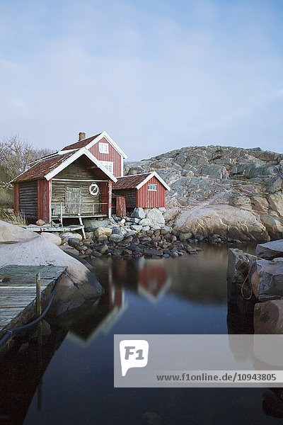Boathouse on rocky shore against sky at sunset