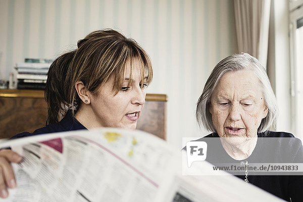 Hausmeisterin mit Seniorin beim Zeitungslesen im Pflegeheim