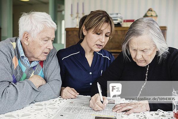 Hausmeisterin unterstützt Seniorin bei der Lösung von Kreuzworträtseln im Pflegeheim
