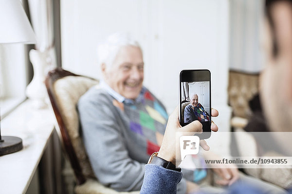 Hausmeister fotografiert Mann durch Smartphone