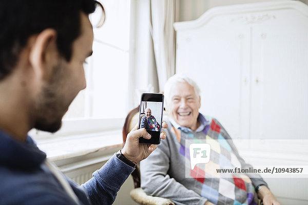 Hausmeister fotografiert glücklichen älteren Mann durch Smartphone im Pflegeheim