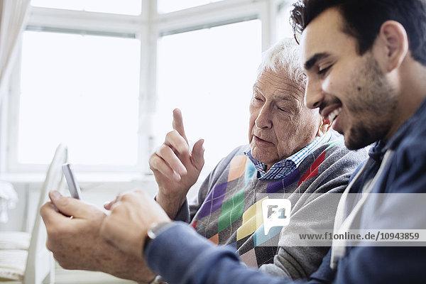 Hausmeister unterstützt den Mann bei der Nutzung des Mobiltelefons im Pflegeheim