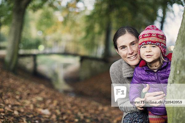 Portrait von Mutter und Tochter  die hinter einem Baum im Park stehen