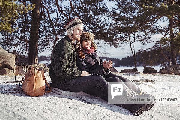 Ein glückliches Paar genießt den Kaffee beim Entspannen auf dem schneebedeckten Feld.