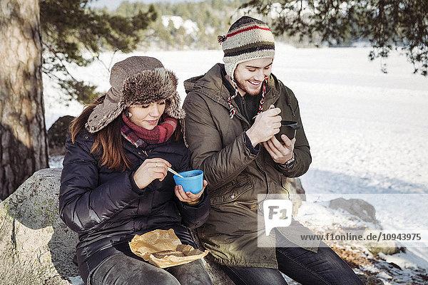 Pärchen  das im Winter auf dem Felsen auf dem Feld sitzt und Nahrung zu sich nimmt.