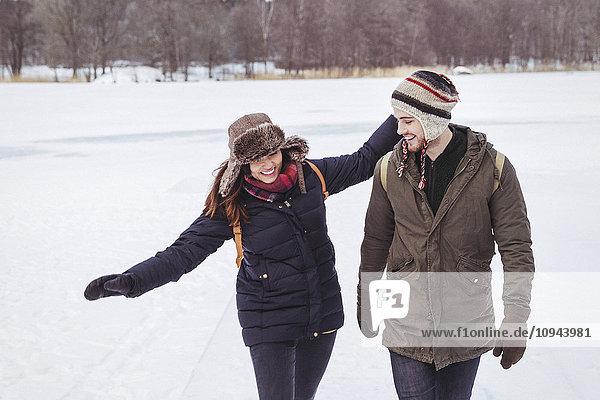 Junger Mann auf der Suche nach einem glücklichen Spaziergang durch die verschneite Landschaft
