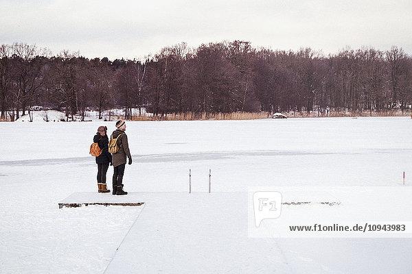 Paar steht auf schneebedecktem Feld gegen den Himmel