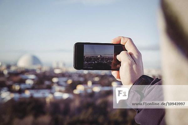 Beschnittenes Bild eines Mannes  der im Winter das Stadtbild mit dem Handy fotografiert.