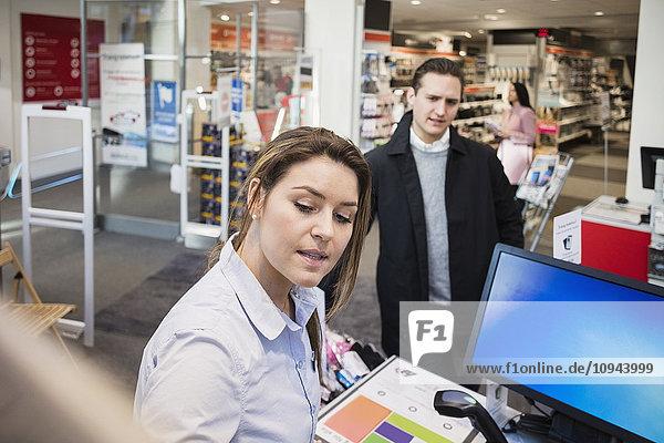 Verkäuferin im Gespräch mit männlichen Kunden an der Kasse im Elektrofachmarkt