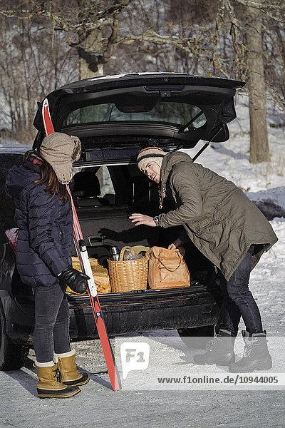 Junger Mann kommuniziert mit Frau beim Beladen des Kofferraums