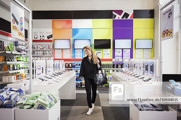 Female customer viewing smart phones in store