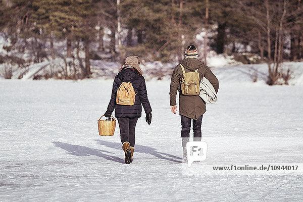 Durchgehende Rückansicht des Paares mit Rucksack auf schneebedecktem Feld