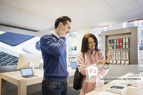 Fröhliche Kundin mit intelligenter Uhr im Stehen mit dem Verkäufer im Geschäft