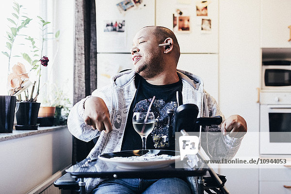 Happy disabled musician with drink sitting by window at recording studio
