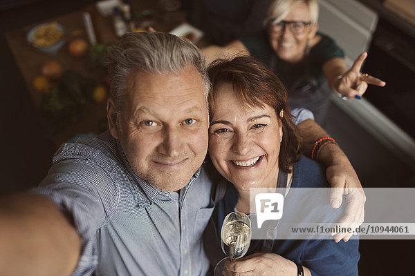Fröhlicher reifer Mann mit Arm um die Frau  während er in der Küche Selfie nimmt.