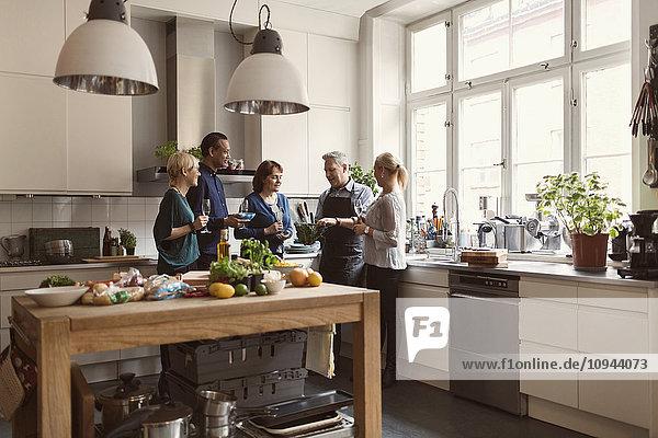 Chefkoch zeigt den Schülern Wirsing im Stehen in der Küche