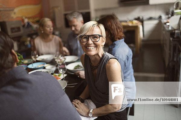 Porträt einer fröhlichen reifen Frau  die mit Freunden am Tisch sitzt.