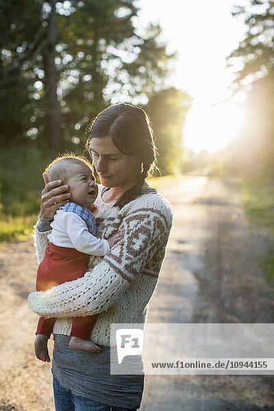 Mutter mit weinendem Baby auf der Straße