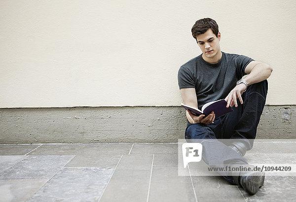 Junger Mann sitzt auf dem Boden und liest ein Buch.