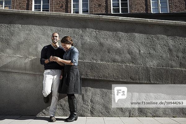 Mittlere erwachsene Freunde  die auf dem Bürgersteig an der Wand stehen und SMS senden