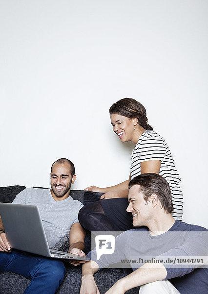 Drei mittelgroße erwachsene Freunde  die zusammen einen Laptop benutzen.