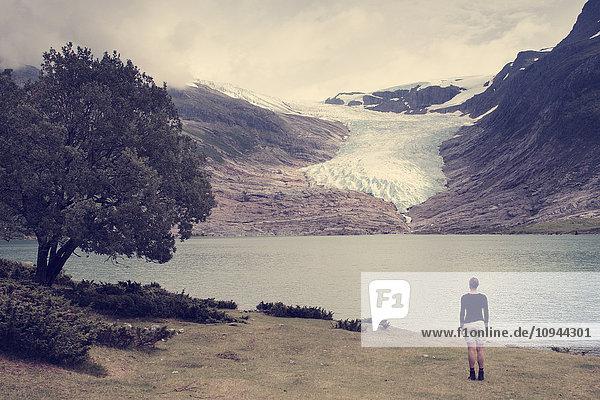 Rückansicht der Frau mit Blick auf See und Berge
