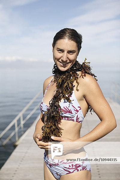 Porträt einer Frau mit Seetang im Bikini im Stehen am Pier
