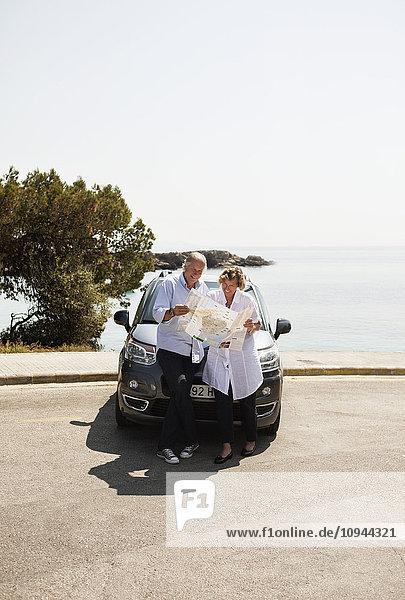 Paar steht vor dem Auto und sucht das nächste Reiseziel in der Karte.