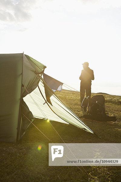 Rückansicht des Menschen mit Zelt auf dem Feld gegen den Himmel bei Sonnenschein