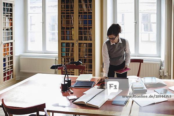 Weibliches Profi-Haltebuch beim Stehen am Tisch in der Bibliothek